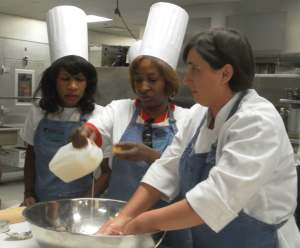 Sous Chef Cynthia Hartzog, right, teaches Visit Knoxville familiarization tour guests Gerri Holmes and Carolyn Daniels the correct way to mix southern-style biscuit batter.